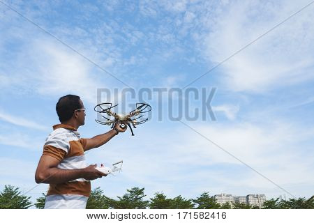Middle-aged man in striped polo T-shirt holding golden drone with four rotors in one hand and remote controller in other against blue sky