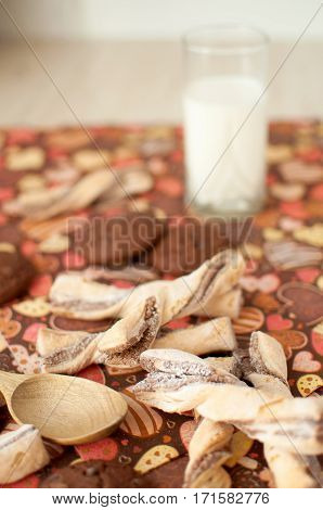 Glass of milk and cookies on dark napkin with image of hearts close up. Selective focus.