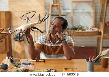 Waist-up portrait of thoughtful Indian repairman sitting at table and analyzing quality of drone with four rotors
