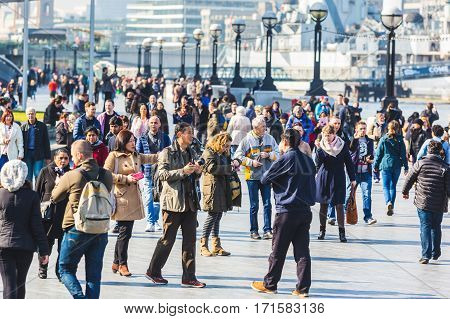 LONDON UNITED KINGDOM - MARCH 20 2015: Crowd of tourists walking on Thames riverside between Tower bridge and London bridge.
