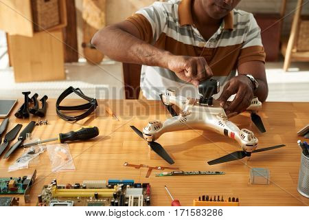 Middle-aged repairman sitting at wooden table and applying machine oil to quadcopter details