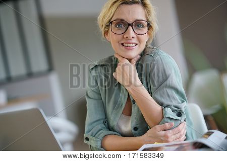 Portrait of blond woman working from home on laptop computer