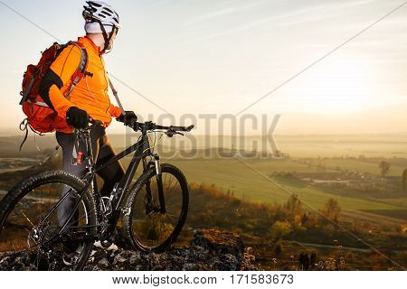 Man with the bike standing on a rock. spring nature. Cyclist in orange jacket, helmet and with red backpack. Healthy traveling in the countryside. Landscape with field, hill and rocks. Background of sky.