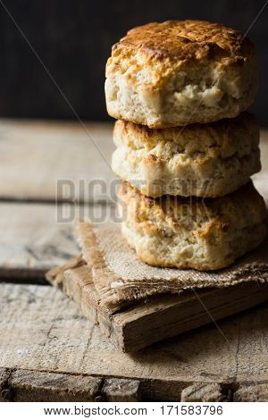 Stack of homemade scones on burlap on vintage wood table black wall rustic kitchen interior minimalistic kinfolknatural light
