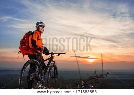 Cyclist leaning against bicycle in front of scenic skyline view of sunset. Landscape with sky and rocks. Cyclist in helmet and sunglasses, with red backpack. Healthy lifestyle. Travel in the countryside.