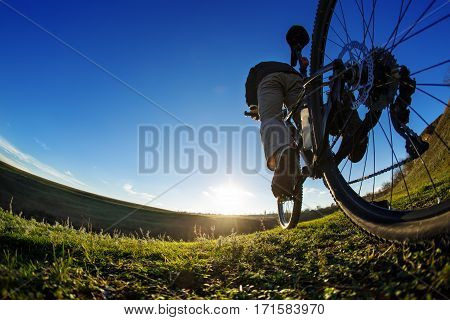 Man on mountain bike rides on the trail on a beautiful sunrise. Bicycle wheel closeup. Wide angle. Fisheye. Background of blue sky. Green field. Grass. Detail of the bicycle. Wheel and pedal. Legs and hand.