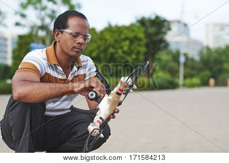 Full-length portrait of concentrated man in safety goggles sitting on haunches in park while fastening camera to quadcopter