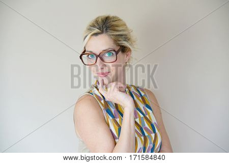Portrait of blond woman with eyeglasses on beige background