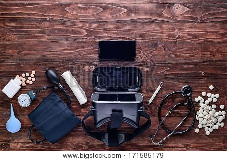 VR glasses,cellphone,drugs,tonometer, stethoscope,bandage, thermometer and enema on wooden table.