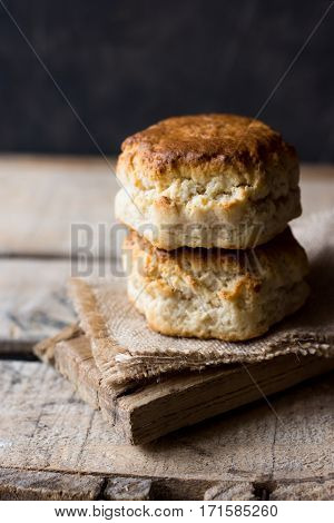 Stack of homemade scones on burlap on vintage wood table black wall rustic kitchen interior minimalistic kinfolk selective focus