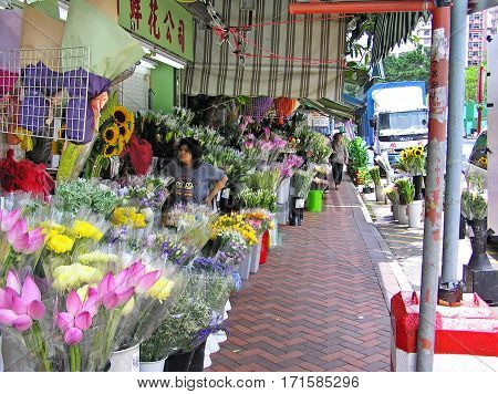 Hong Kong, China - March 23, 2003: A saleswoman stands in front of a flower shop on the flower market in Hong Kong. She is surrounded by many colorful flowers. From behind another woman walks up.