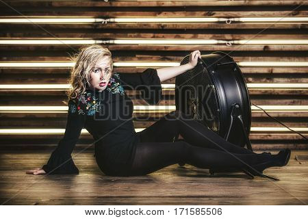 Woman Model Beautiful And Fashionable On The Background Of A Wooden Wall With A  Light With Ventilat