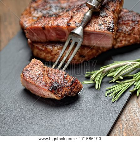 grilled juicy steak with rosemary on a gray background