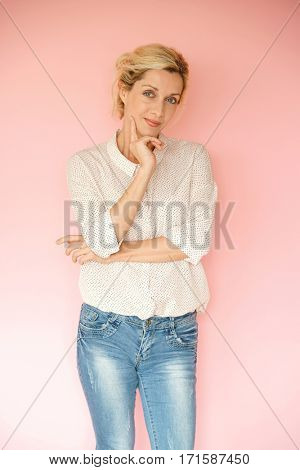 Blond woman in blue jeans standing on pink background