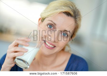 Portrait of blond mature woman drinking milk from glass