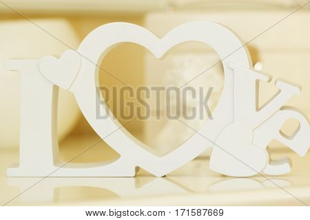 Wooden letters forming word LOVE written with angel on background