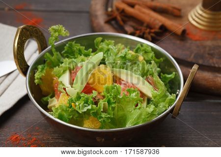 Vegan and vegetarian dish, fresh vegetable salad in copper bowl. Indian restaurant, lettuce and fruits mix with herbs, healthy meal, closeup on wood background. Eastern local cuisine food.