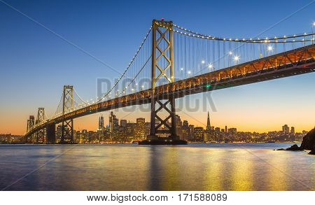 Classic panoramic view of famous Oakland Bay Bridge with the skyline of San Francisco illuminated in beautiful twilight after sunset in summer California USA