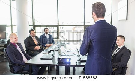 Successful team leader and business owner leading informal in-house business meeting. Business people with laptops in modern corporate office. Business and entrepreneurship concept.