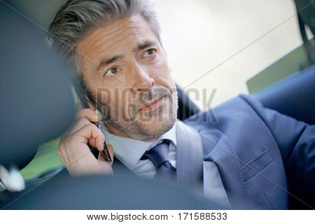 Businessman talking on phone in taxi cab