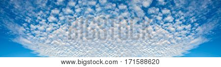 Panorama of blue sky and the shapes of flying clouds. Heavenly background in a highly patterned top. Free space atmospheric flight and freedom.