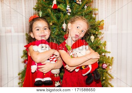 Portrait of two children girls around a Christmas tree decorated. Kid on holiday new year