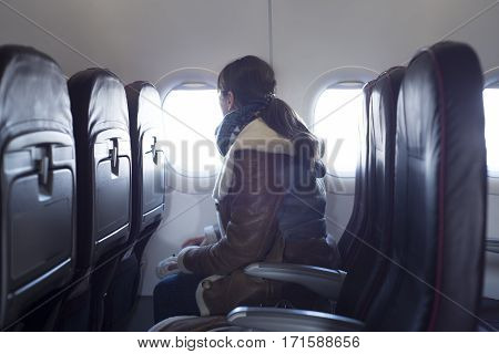 Young woman is on passenger seat at airplane looking outside