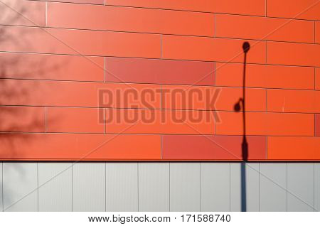 The front facade of a modern building of gray and red panels. Shadows of the trees and Street lamp on the facade of the building. Architectural background.