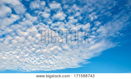 Blue sky and the shapes of flying clouds. Heavenly background in a highly patterned top. Free space atmospheric flight and freedom.