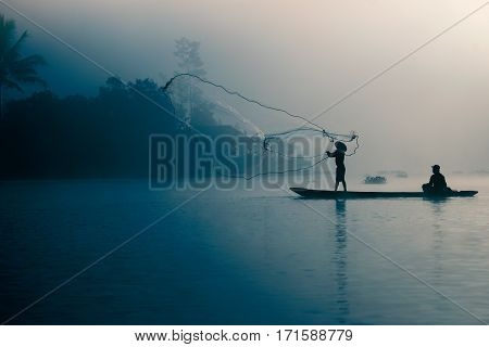Fisherman casting out his fishing net early in the morning.