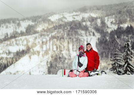Man In Red Ski Jacket Lies His Hand On Woman's Shoulder While They Pose On Snowed Hill In The Mounta
