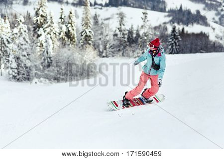 Woman In Ski Suit Looks Over Her Shoulder Going Down The Hill On Her Snowboard