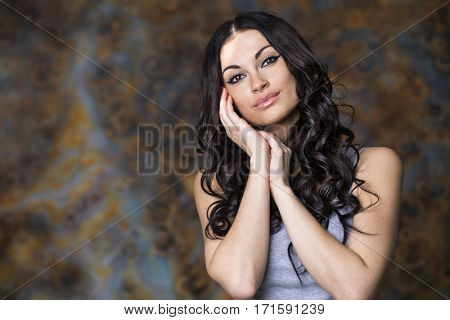 Close-up portrait of a young woman. Beautiful brunette burning on dark background studio wall