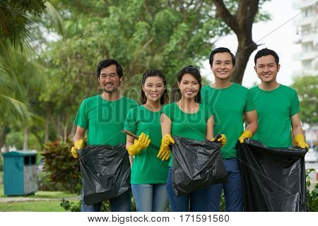 Enthusiastic group of Asian volunteers standing in park with bin bags before starting to collect garbage