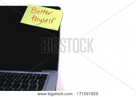 Self Improvement memo stuck on laptop computer.