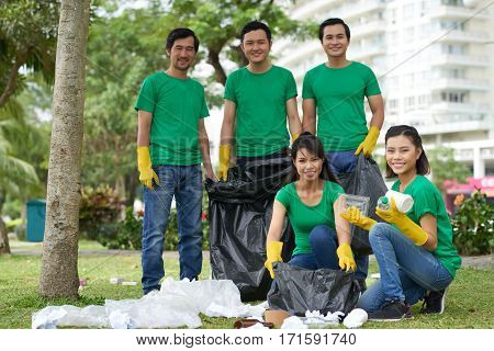 Young Asian male and female activists in green T-shirts collecting and sorting trash in city park