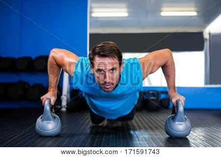 Portrait of serious man doing push-ups with kettlebell in gym