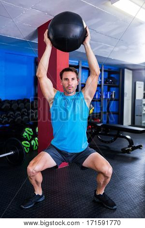 Portrait of serious athlete holding exercise ball in gym