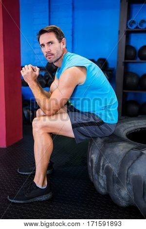 Portrait of serious male athlete sitting on tire in gym
