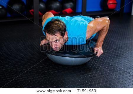 Serious man using BOSU ball while exercising in gym