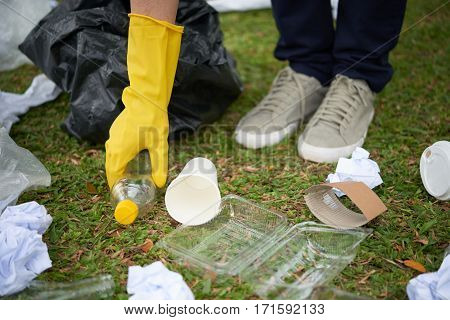 Close-up shot of plastic waste lying on grass, human hand taking bottle in order to put it into bin bag
