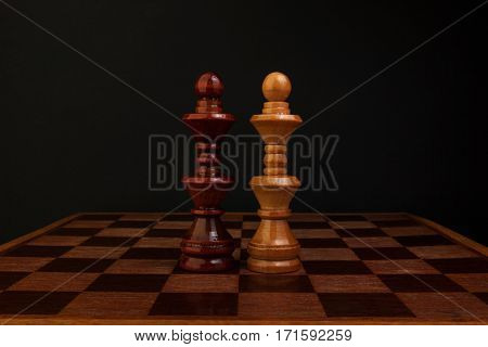 Chess. Black and white King on wood board.