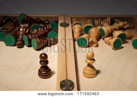 Chess. The idea - face to face, close up. Chess pieces in a wooden box inside.