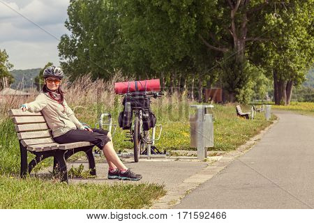 Female cyclist traveling on a bicycle with a load. Female cyclist traveling on a bicycle with a load. The woman is sitting on the bench looking at the camera and smiling.