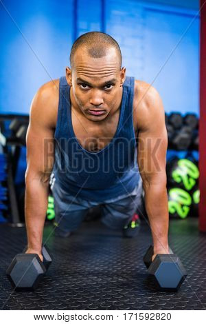 Portrait of serious male athlete doing push-ups with dumbbells in gym