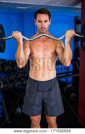 Serious athlete holding barbell in gym
