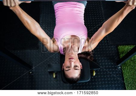 High angle view of woman holding barbell while lying on bench press in gym