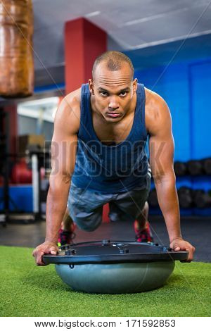 Portrait of serious young athlete with BOSU ball while exercising in gym