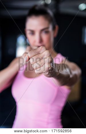 Portrait of female athlete punching in gym