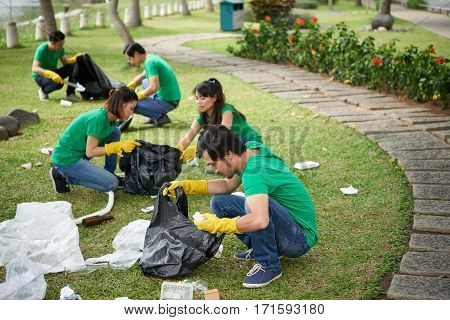 Group of five friends sitting on haunches in lovely park while taking garbage from grass and putting it into bin bags